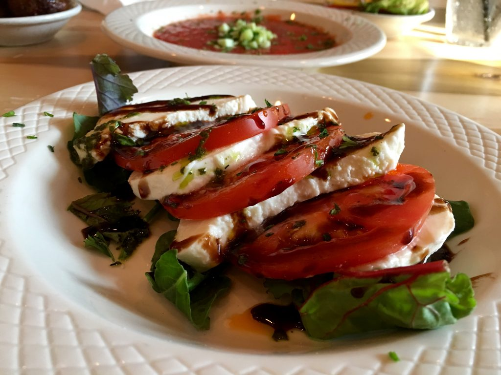 Caprese salad with a generous amount of balsamic reduction and fresh herbs/greens.